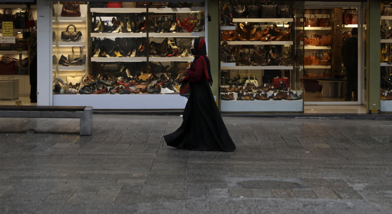 A woman wearing a face mask as a preventive measure against the spread of the new coronavirus walks past shoe shops in a mostly empty street in a commercial district in downtown Tehran, Iran, Sunday, March 22, 2020. on Sunday, Iran imposed a two-week closure on major shopping malls and centers across the country to prevent spreading the virus. Pharmacies, supermarkets, groceries and bakeries will remain open. (AP Photo/Vahid Salemi)