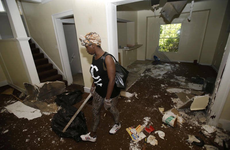 Sanautica Hicks-Ross, 18, searches an abandoned home Sunday, July 21, 2013, near where three bodies were found in East Cleveland, Ohio. Hicks-Ross is an East Cleveland resident. Police Chief Ralph Spotts told volunteers checking vacant houses in a neighborhood where three bodies were found wrapped in plastic bags that he believes there could be one or two more victims. (AP Photo/Tony Dejak)
