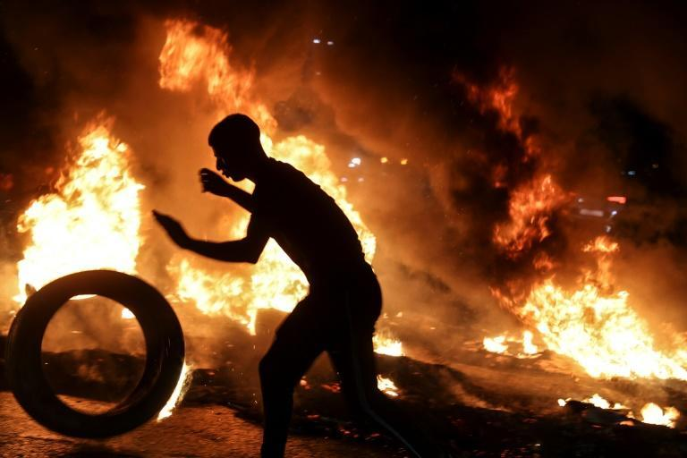 A youth prepares to set a tyre ablaze during confrontations with Israeli security forces in Nablus after a rally in support of the Palestinian escapees (AFP/Jaafar ASHTIYEH)