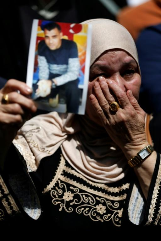 A woman holds the portrait of a Palestinian prisoner during a rally in the West Bank city of Ramallah  on April 17, 2017 to show support to hundreds of hunger strikers in Israeli jails