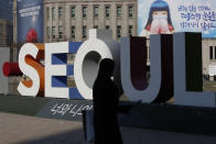 A woman wearing a face mask as a precaution against the coronavirus walks near the display of South Korea's capital Seoul logo in Seoul, South Korea on Dec. 21, 2020. South Korea had seemed to be winning the fight against the coronavirus: Quickly ramping up its testing, contact-tracing and quarantine efforts paid off when it weathered an early outbreak without the economic pain of a lockdown. But a deadly resurgence has reached new heights during Christmas week, prompting soul-searching on how the nation sleepwalked into a crisis. (AP Photo/Lee Jin-man)