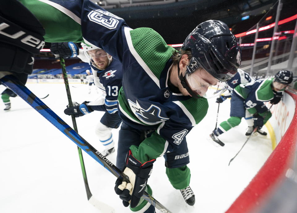 Vancouver Canucks defenseman Quinn Hughes (43) fights for control of the puck with Winnipeg Jets center Pierre-Luc Dubois (13) during second-period NHL hockey game action in Vancouver, British Columbia, Sunday, Feb. 21, 2021. (Jonathan Hayward/The Canadian Press via AP)