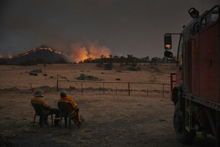 Volunteer firefighters watch as a bushfire rages on the outskirts of the town of Tumbarumba in New South Wales (AFP Photo/Kiran Ridley)