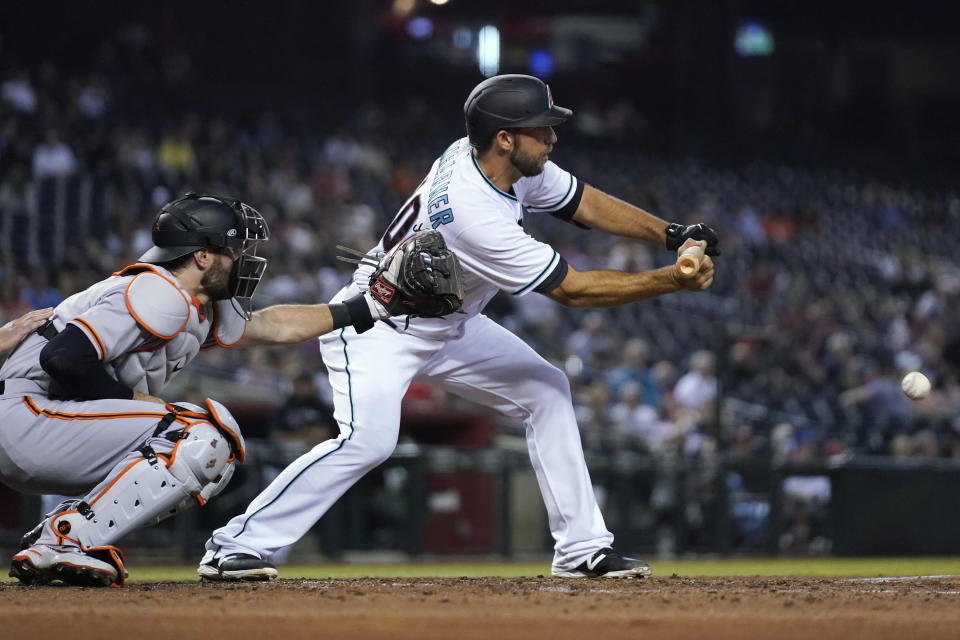 Arizona Diamondbacks' Madison Bumgarner, right, drops down a sacrifice bunt next to San Francisco Giants catcher Curt Casali during the fourth inning of a baseball game, Tuesday, Aug. 3, 2021, in Phoenix. (AP Photo/Ross D. Franklin)