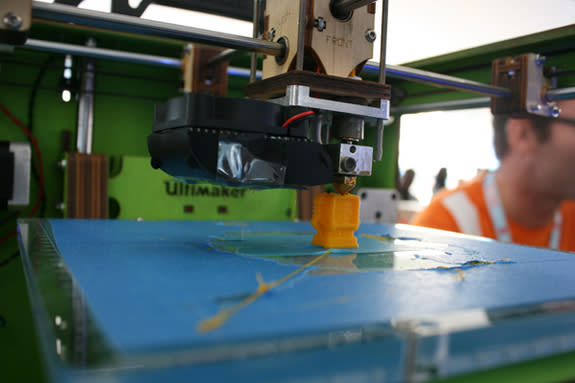 The Ultimaker churns out a tiny, yellow robot figurine.