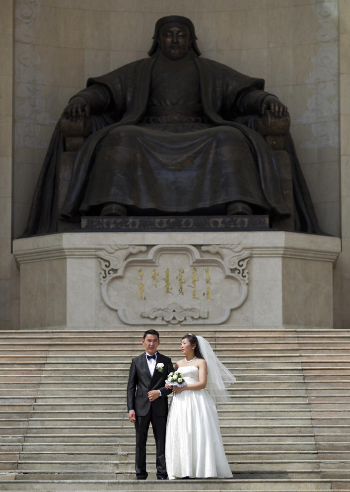 In this July 2, 2012 photo, a newlywed couple poses for their wedding photos in front of a statue of Genghis Khan at the Parliament House on the ground of Sukhbaatar Square in Ulan Bator, Mongolia. Landlocked with 2.8 million people spread over an area twice the size of Texas, Mongolia is dwarfed by China, with its 1.3 billion people and the world's second largest economy. Fully 90 percent of Mongolia's exports - coal, copper, cashmere and livestock - go to China, which in turn sends machinery, appliances and other consumer goods that account for a third of Mongolian imports. (AP Photo/Andy Wong)