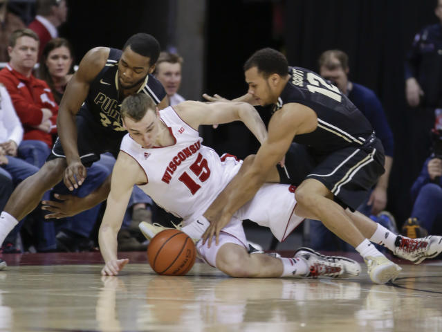 Wisconsin's Sam Dekker (15) battles against Purdue's Errick Peck, left, and Bryson Scott (12) for a loose ball during the second half of an NCAA college basketball game Wednesday, March 5, 2014, in Madison, Wis. Wisconsin won 76-70. (AP Photo/Andy Manis)