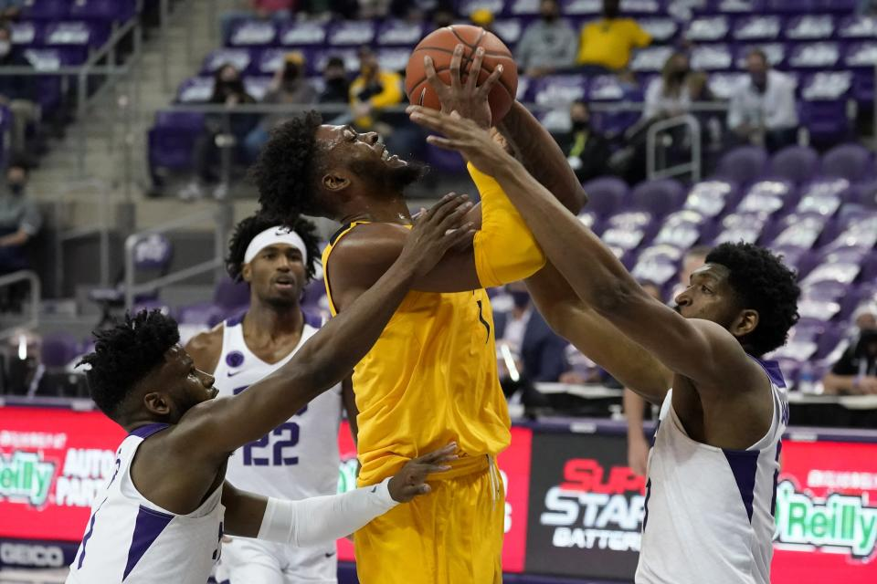 TCU guard Mike Miles, left, and center Kevin Samuel, right, defend as West Virginia forward Derek Culver, center, attempts a shot in the first half of an NCAA college basketball game in Fort Worth, Texas, Tuesday, Feb. 23, 2021. (AP Photo/Tony Gutierrez)