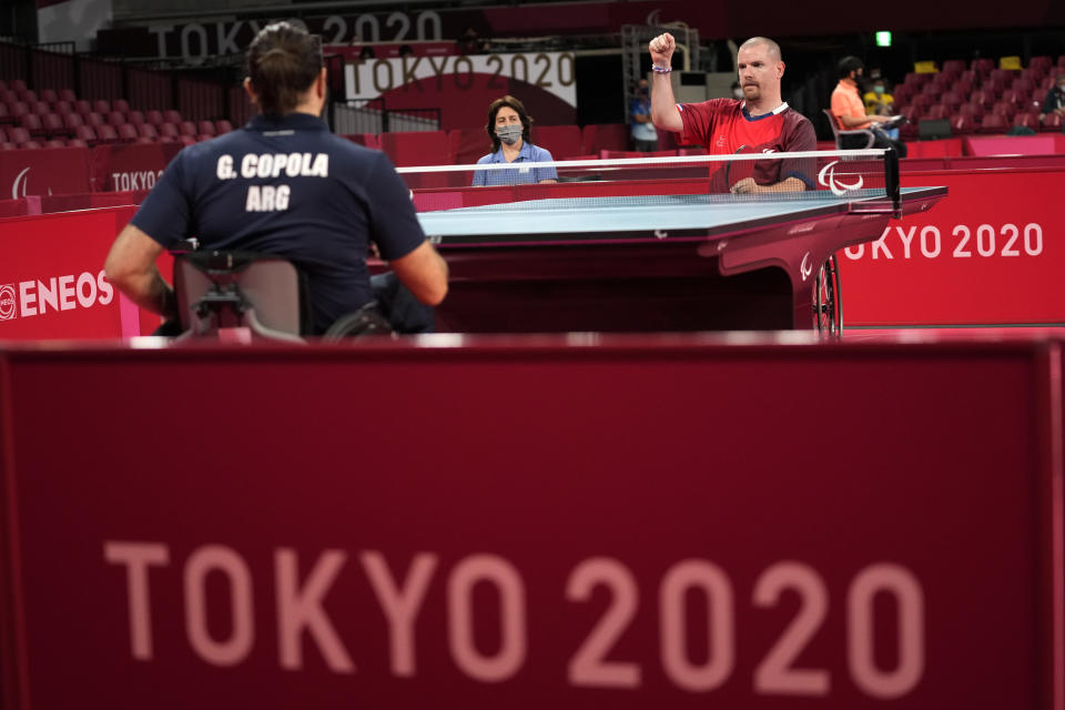 Florian Merrien, top right, of France and Gabriel Copola, top left, of Argentin play in Class 3, Group C of men's table tennis competition at the Tokyo 2020 Paralympic Games Wednesday, Aug. 25, 2021, in Tokyo, Japan. (AP Photo/Eugene Hoshiko)