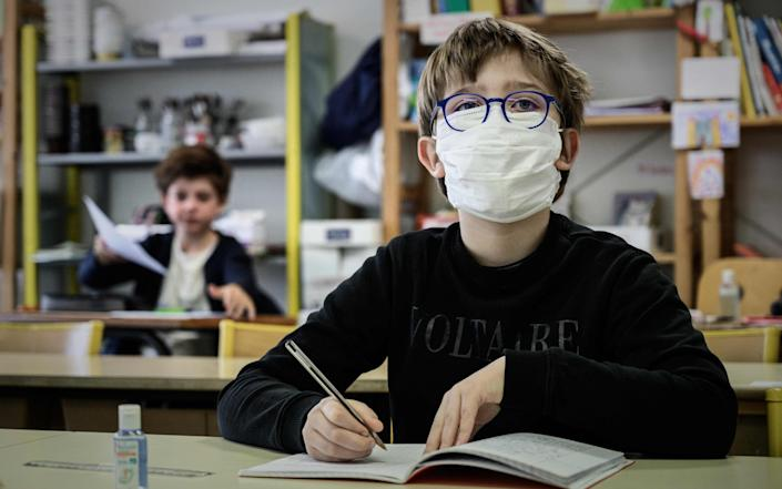 A pupil wearing a facemask attends a class at the private school Institut Sainte Genevieve in Paris - AFP