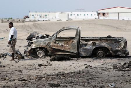 FILE PHOTO: Man inspects the wreckage of a government forces vehicle destroyed by UAE air strikes near Aden