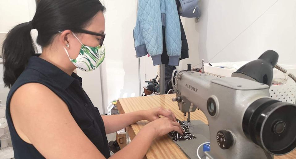 Valerie Diola shown at her sewing machine.