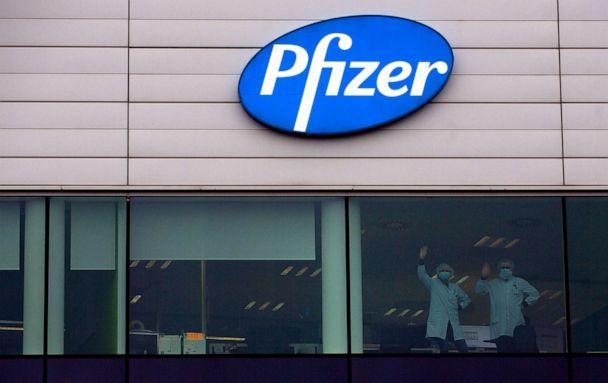 PHOTO: Two workers wave from a window at Pfizer Manufacturing in Puurs, Belgium, Dec. 2, 2020. British officials authorized a COVID-19 vaccine for emergency use, greenlighting the world's first shot against the virus. (Virginia Mayo/AP)