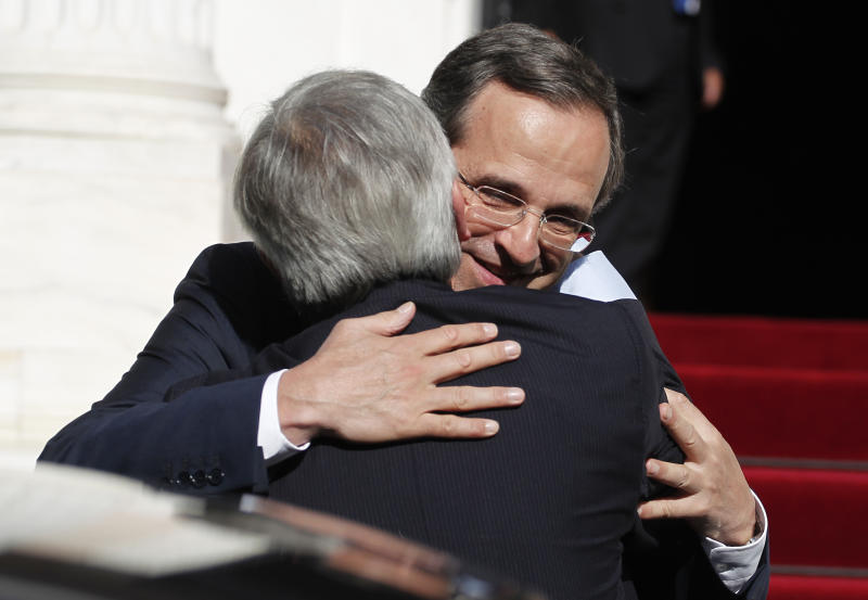 Greek Prime Minister, Antonis Samaras, right, embraces Claude Junker, Prime Minister of Luxembourg and President of Eurogroup prior to their meeting in Athens, Wednesday, Aug. 22, 2012. Juncke insisted Greece must remain within the euro. Its exit from the currency used by 17 European Union countries would hurt both the country and the wider continent. (AP Photo/Petros Giannakouris)