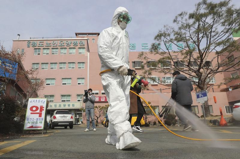 A worker in protective medical gear sprays disinfectant outside a South Korea hospital.