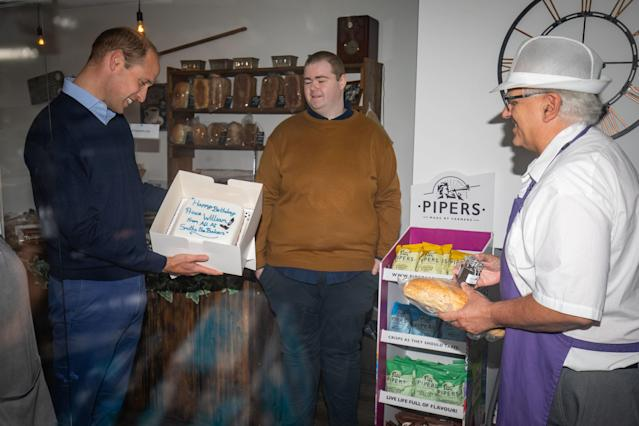 Prince William is presented by shop owner Paul Brandon (R) with a birthday cake. (Getty Images)