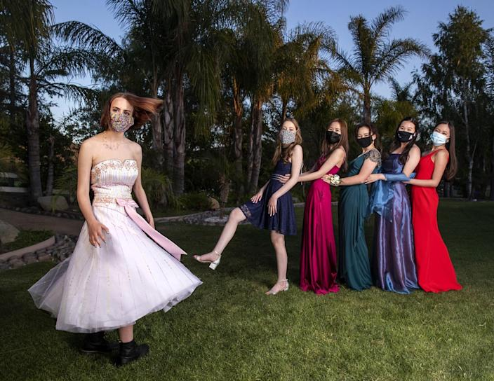 The students pose in masks and formal robes.