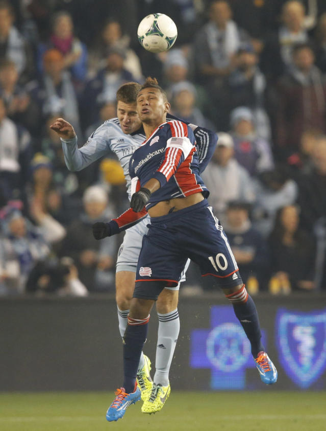 New England Revolution forward Juan Agudelo (10) and Sporting Kansas City defender Matt Besler, back, vie for a head ball during the first half of an MLS playoff soccer match in Kansas City, Kan., Wednesday, Nov. 6, 2013. (AP Photo/Orlin Wagner)