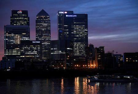 A river ferry passes in front of the Canary Wharf business district at dusk in London