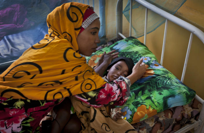 A Somali mother cares for her child in an isolation ward full of children with measles or meningitis at the Benadir hospital in Mogadishu, Somalia Wednesday, April 24, 2013. On the eve of the Global Vaccine Summit in Abu Dhabi and coinciding with World Immunization Week, the authorities in Somalia, which has one of the lowest immunization rates in the world, have launched a new push to vaccinate against several potentially fatal childhood diseases. (AP Photo/Ben Curtis)