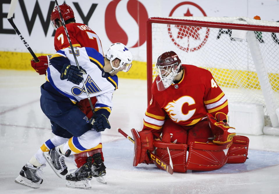 St. Louis Blues' David Perron, center, is hit in the shin by a slap shot as Calgary Flames goalie Mike Smith watches during the third period of an NHL hockey game Saturday, Dec. 22, 2018, in Calgary, Alberta. (Jeff McIntosh/The Canadian Press via AP)