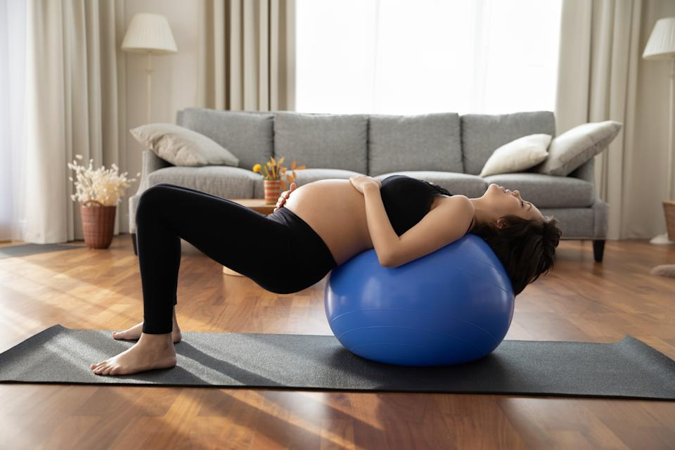 Concentrated pregnant woman doing exercises with fitness ball at home, practicing yoga, pilates with support on fitball, training body, core muscles. Sport activity in pregnancy, prenatal care concept