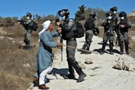 A Palestinian man confronts Israeli security forces after they intervened in scuffles earlier between Jewish settlers and Palestinian farmers in the West Bank