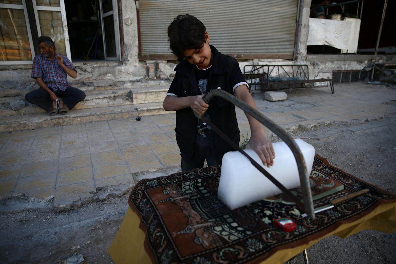 A boy cuts ice during Ramadan in the rebel held besieged eastern Damascus suburb of Ghouta, Syria May 28, 2017. REUTERS/Bassam Khabieh