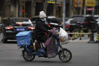 A food delivery worker wearing a face mask to help curb the spread of the coronavirus rides on a street in Beijing on Thursday, Jan. 14, 2021. The e-commerce workers and delivery people who kept China fed during the pandemic, making their billionaire bosses even richer, are so unhappy with their pay and treatment that one just set himself on fire in protest. (AP Photo/Andy Wong)
