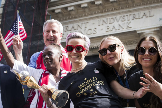 Megan Rapinoe #15 of United States holds the 2019 FIFA World Cup Champion Trophy with Alex Morgan #13 of United States and Allie Long #20 of United States, Mayor Bill De Blasio, and his wife Chirlane McCray ride on the World Champions float as it rides down Broadway for the Ticker Tape through the Canyon of Heroes. This celebration was put on by the City of Manhattan to honor the team winning the 2019 FIFA World Cup Championship title, their fourth, played in France against Netherlands, at the City Hall Ceremony in the Manhattan borough of New York on July 10, 2019, USA. (Photo by Ira L. Black/Corbis via Getty Images)