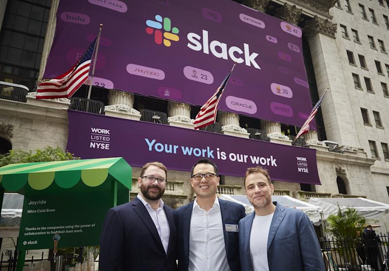 Three men in business attire standing in front of a Slack banner in front of the New York Stock Exchange.
