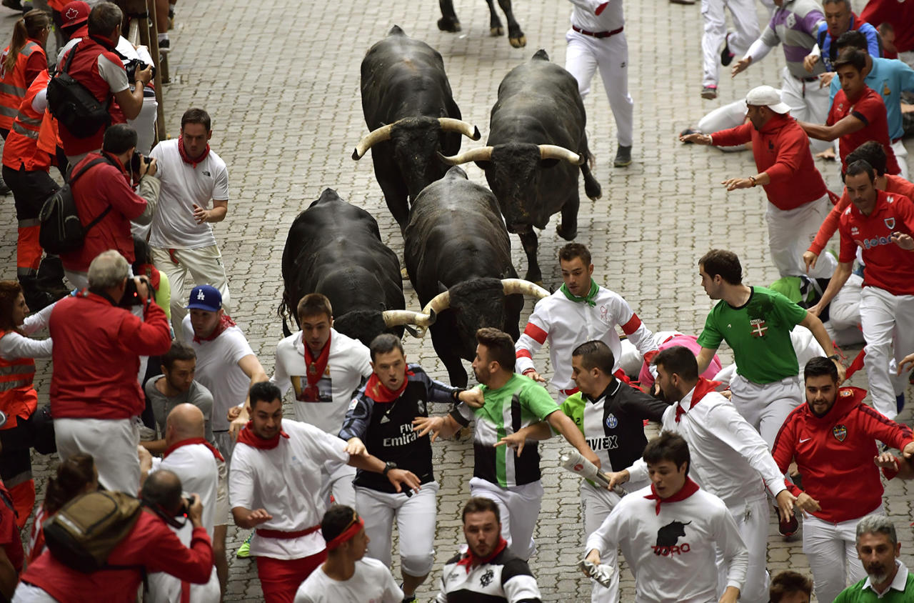 <p>Revellers run in front of Miura's fighting bulls during the running of the bulls at the San Fermin Festival, in Pamplona, northern Spain, July 14, 2017. (Photo: Alvaro Barrientos/AP) </p>