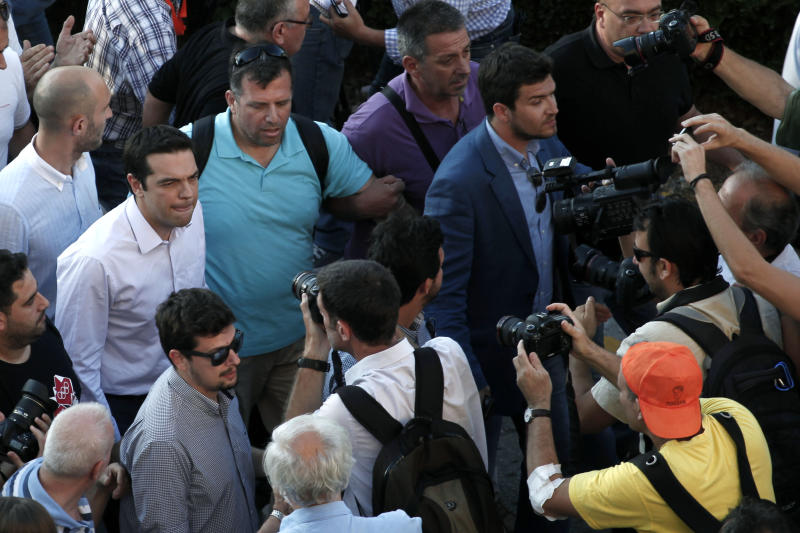 Greece's Left-wing opposition leader Alexis Tsipras, left with a white shirt , walks during his visit at Greek state television ERT headquarters in Athens, on Wednesday, June 19, 2013. Fired ERT employees have continued unauthorized broadcasts since the broadcaster's June 11 closure, streamed mostly online and on disused analog frequencies. Greece's governing coalition parties met for a second time in three days to try and end a political crisis triggered by the closure of state broadcaster ERT.(AP Photo/Petros Giannakouris)