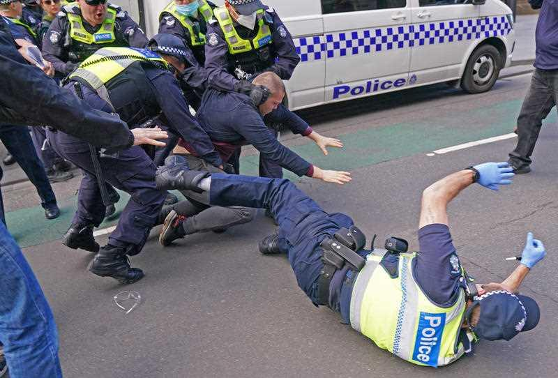 A police officer falls to the ground as officers try to detain a man while protesters gather outside Parliament House in Melbourne.