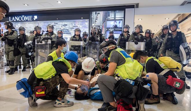 Medical volunteers render aid to a demonstrator inside New Town Plaza shopping mall on Sunday. Photo: Bloomberg