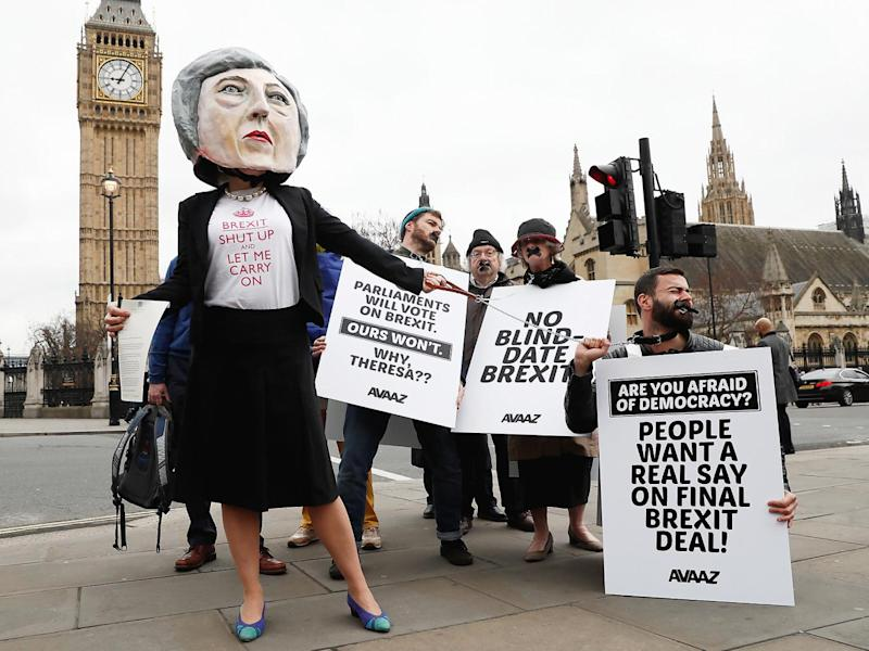 Anti-Brexit protesters, one wearing a giant Theresa May head, hold placards outside Parliament on the day the Prime Minister will announce that she has triggered the process by which Britain will leave the European Union (Reuters)