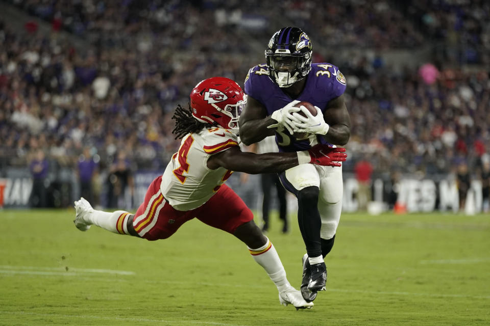 Baltimore Ravens running back Ty'Son Williams (34) rushes past Kansas City Chiefs linebacker Nick Bolton in the first half of an NFL football game, Sunday, Sept. 19, 2021, in Baltimore. (AP Photo/Julio Cortez)