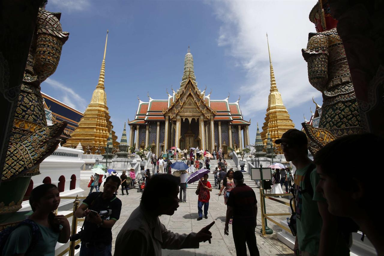 Tourists visit the Grand Palace in Bangkok May 24, 2014. The Thai army's imposition of martial law is another blow to the country's tourist industry, adding to the economic pain from six months of destabilizing street protests as airlines cut back on flights and concern over insurance adds to travelers' worries. Tourism officials put a brave face on the latest twist in the long-running civil strife, saying it was too early to gauge the impact on tourist arrivals, which already dipped nearly 6 percent in the first three months of the year. REUTERS/Erik De Castro (THAILAND - Tags: POLITICS TRAVEL CIVIL UNREST BUSINESS)