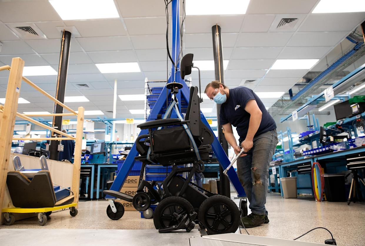 Lead technician Brian Dean is seen installing a test seat to perform a final acceptance test of the iBOT power base on May 4, 2021, at Mobius Mobility headquarters in Manchester, New Hampshire. (Kayana Szymczak for Yahoo News)