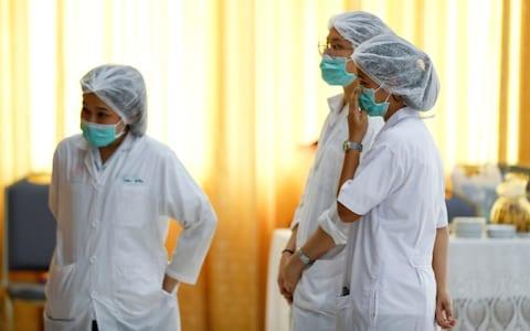 <span>A nurse adjusts her face mask at Chiang Rai hospital</span> <span>Credit: Vincent Thian /AP </span>