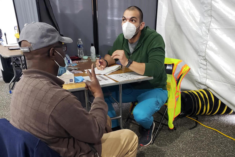 In this March 12, 2021 photo provided by Unity Health Care, Othon Sosua, right, talks with a patient during a vaccination drive in Washington, D.C. Homeless Americans who have been left off priority lists for coronavirus vaccinations — or even bumped aside as states shifted eligibility to older age groups — are finally getting their shots as vaccine supplies increase. Walk-up vaccine events are crucial for a population with limited access to cars, cellphones or Wi-Fi, organizers say. (Unity Health Care via AP)