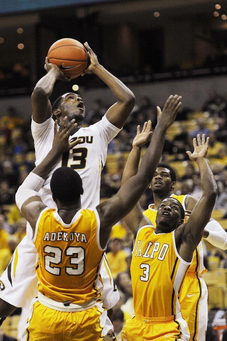 Missouri's Montaque Gill-Caesar, top, shoots over Valparaiso's Jubril Adekoya, bottom left, and Max Joseph, right, during the first half of an NCAA college basketball game Sunday, Nov. 16, 2014, in Columbia, Mo. (AP Photo/L.G. Patterson)