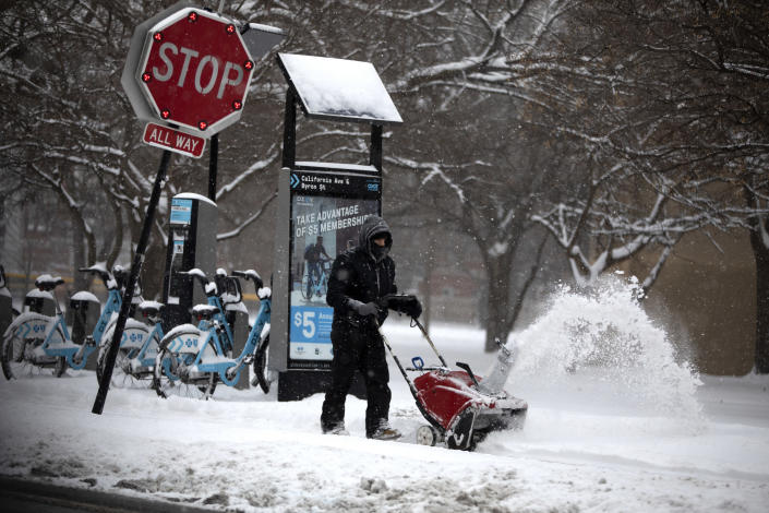 Snow is removed from the sidewalk in front of the McFetridge Sports Center Saturday, Jan. 19, 2019, in Chicago. (Erin Hooley/Chicago Tribune via AP)