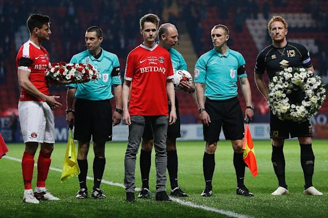 John Palmer (C), brother of Charlton Athletic season ticket holder, PC Keith Palmer, who was killed in the March 22, 2017 Westminster terror attack, greets match officials and players at The Valley Stadium in London (AFP Photo/Adrian DENNIS)