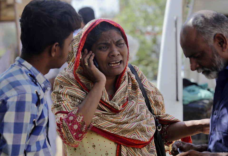 A woman mourns while talking on cell phone after she identified a body of her family member, who was killed in the Friday's plane crash, at a morgue in Karachi, Pakistan, Saturday, May 23, 2020. An aviation official says a passenger plane belonging to state-run Pakistan International Airlines carrying passengers and crew has crashed near the southern port city of Karachi. (AP Photo/Fareed Khan)