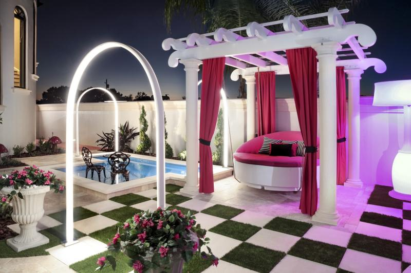 This 2019 photo provided by Ryan Hughes of Ryan Hughes Design Build shows an outdoor space at a home in Florida. Tampa-based designer Hughes took inspiration from the homeowner's daughter's love of Alice in Wonderland to create a playful, over-the-top outdoor space complete with unique lighting effects, a hanging bed and oversized checkerboard. (Joe Traina/Ryan Hughes via AP)