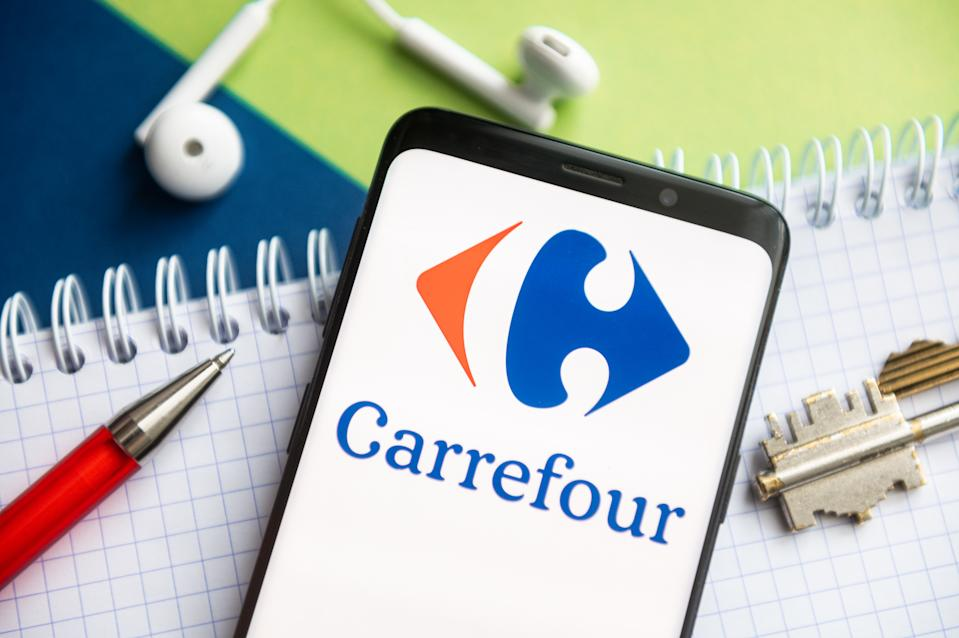 POLAND - 2021/02/09: In this photo illustration, a Carrefour logo seen displayed on a smartphone with a pen, key, book and headsets in the background. (Photo Illustration by Mateusz Slodkowski/SOPA Images/LightRocket via Getty Images)