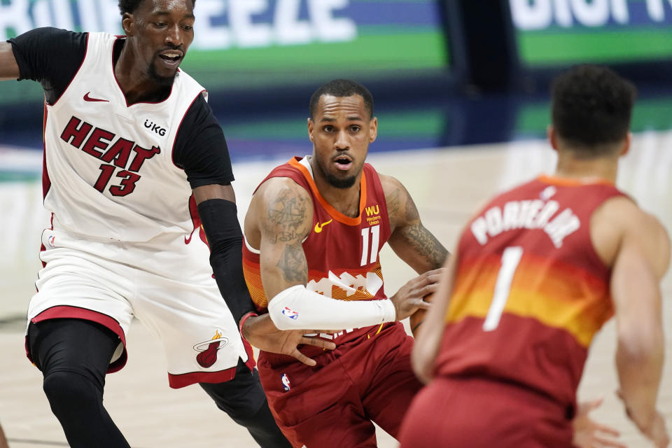 Denver Nuggets guard Monte Morris, center, looks to pass the ball to forward Michael Porter Jr., right, as Miami Heat center Bam Adebayo defends in the first half of an NBA basketball game Wednesday, April 14, 2021, in Denver. (AP Photo/David Zalubowski)