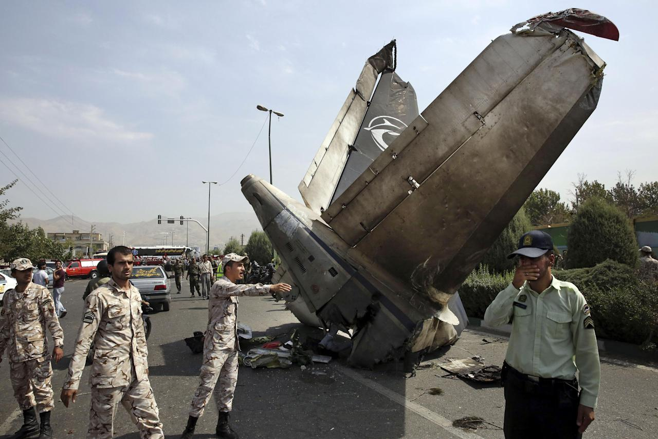 Iranian Revolutionary Guards and police officers inspect the site of a passenger plane crash near the capital Tehran, Iran, Sunday, Aug. 10, 2014. An Iranian passenger plane crashed Sunday while taking off from an airport near the capital, killing tens of people onboard, state media reported. (AP Photo/Vahid Salemi)