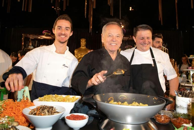 Wolfgang Puck (C) and his son Byron Puck (L) prepare a dish during the Governors Ball press preview in Hollywood on January 31 (AFP Photo/VALERIE MACON)